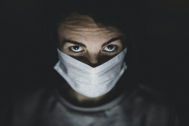Man in Medical Mask in dark room
